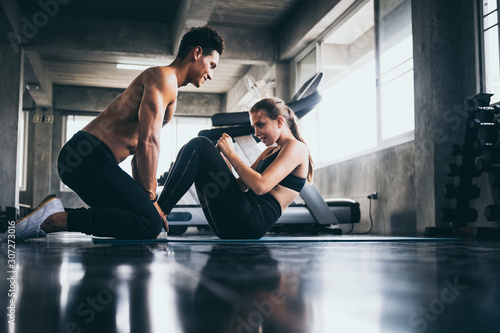 Fotografia Personal trainer helping woman exercising in the sport gym