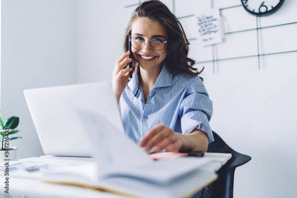 Fototapeta Smiling brown haired woman talking on smartphone in office