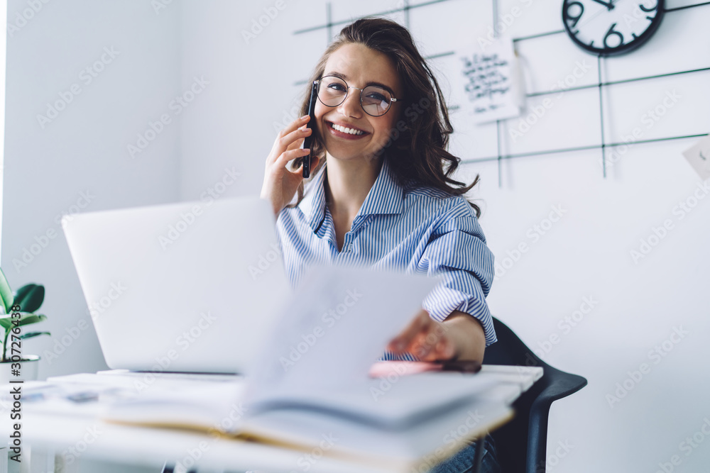 Fototapeta Young woman laughing while talking on cellphone in office
