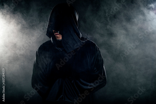 Obraz na plátně Man dressed in a dark robe looking like a cult leader on a smoky or foggy background