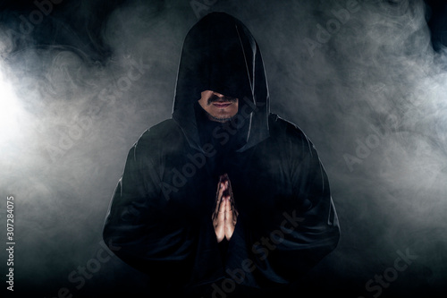 Photo Man dressed in a dark robe looking like a cult leader on a smoky or foggy background