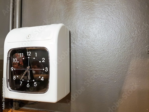 Photo Time stamp clock for employee check in attendance for their working time located in the gate of factory, office area, workplace object working hour control