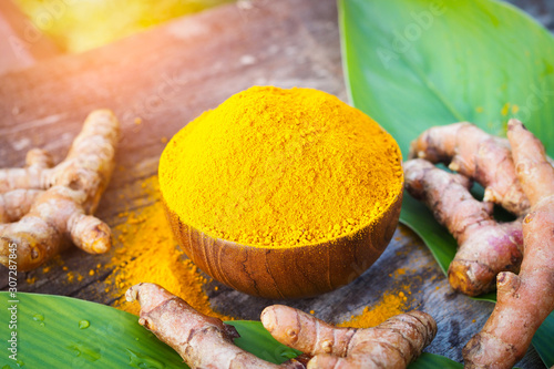 Obraz Turmeric powder and fresh turmeric in wooden bowls on old wooden table. Herbs - fototapety do salonu