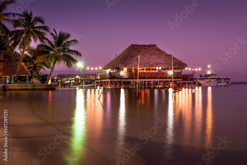 Photo A view of the bungalow overwater beautifully lit up at dusk in Belize