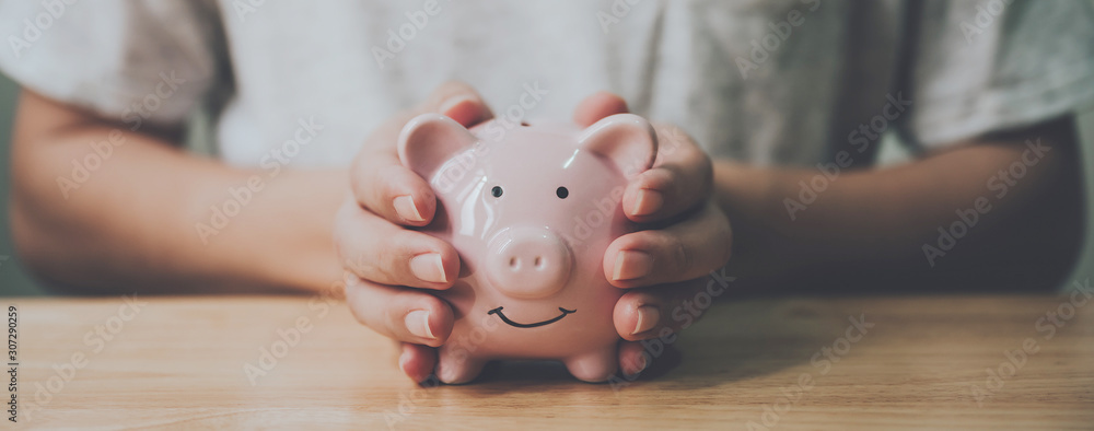 Fototapeta Panoramic image, Man hand holding piggy bank on wood table. Save money and financial investment