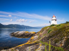 White Lighthouse Tower With Red Top And Moss Covered Rocky Shore Of The Sognefjord In Norway On A Sunny Day, With Mountains, Blue Sky And Fluffy White Clouds.