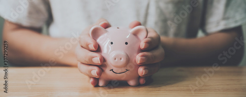 Fototapeta Panoramic image, Man hand holding piggy bank on wood table