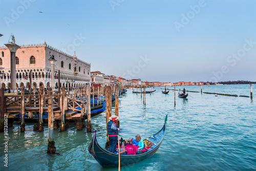 Spoed Fotobehang Gondolas Venetian gondolier punting gondola through green canal waters of Venice Italy