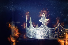 Low Key Image Of Beautiful Queen/king Crown Over Antique Box Next To Sword. Fantasy Medieval Period. Selective Focus. Glitter Sparkle Lights Ans Flames Fire