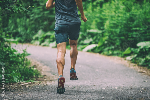 Leinwand Poster Runner man athlete jogging in city run on park path running view from back summer outdoor green forest