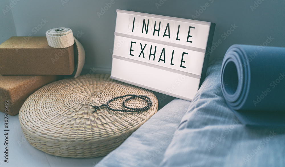 Fototapeta Yoga breathing INHALE EXHALE sign at fitness class on lightbox inspirational message with exercise mat, mala beads, meditation pillow. Accessories for fit home lifestyle.