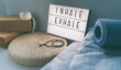 canvas print picture - Yoga breathing INHALE EXHALE sign at fitness class on lightbox inspirational message with exercise mat, mala beads, meditation pillow. Accessories for fit home lifestyle.