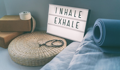 Yoga breathing INHALE EXHALE sign at fitness class on lightbox inspirational message with exercise mat, mala beads, meditation pillow. Accessories for fit home lifestyle.