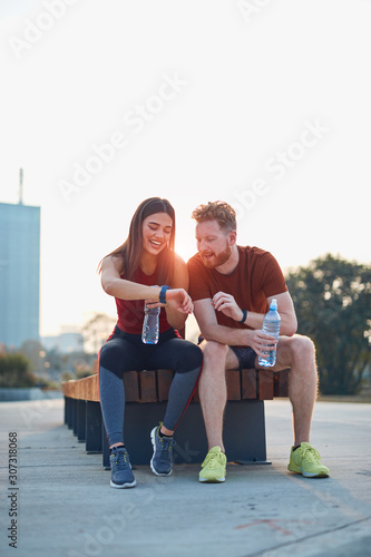 obraz PCV Modern couple making pause in an urban park during jogging / exercise.