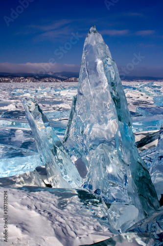 A large broken transparent piece of ice stands frozen vertically on Lake Baikal. A lot of broken ice around. Beautiful blue and green color of ice. Vertical.