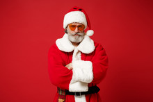 Serious Elderly Gray-haired Mustache Bearded Santa Man In Christmas Hat, Sunglasses Posing Isolated On Red Background. Happy New Year 2020 Celebration Concept. Mock Up Copy Space. Hold Hands Crossed.