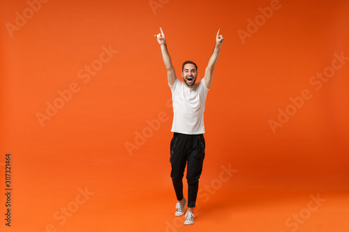 Fototapeta Funny young man in casual white t-shirt posing isolated on orange background, studio portrait. People sincere emotions lifestyle concept. Mock up copy space. Rising hands, pointing index fingers up. obraz