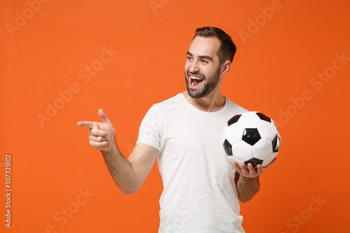 Photo Cheerful young man in casual white t-shirt posing isolated on orange background in studio