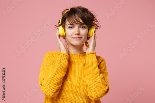 Obraz na płótnie Beautiful young brunette woman girl in yellow sweater posing isolated on pastel pink wall background studio portait