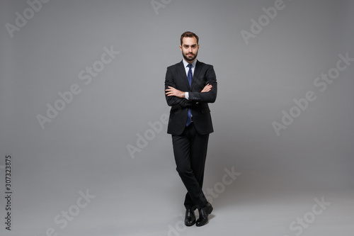 Obraz Handsome young bearded business man in classic black suit shirt tie posing isolated on grey background in studio. Achievement career wealth business concept. Mock up copy space. Holding hands crossed. - fototapety do salonu