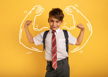 Young Boy Student Acts Like A Muscled Man. Yellow Background