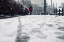 Low Angle Shot Of A Person Walking On The Snow Covered Sidewalk Under The Snow
