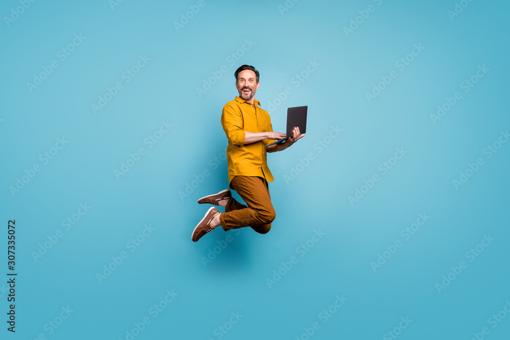 Fototapeta Full size photo of funky man feel rejoice emotions jump use laptop search social media online black friday discounts wear casual style clothing isolated over blue color background