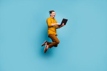 Full body photo of cheerful excited man jump use computer search online social media black friday sales discounts wear casual style clothes isolated over blue color background