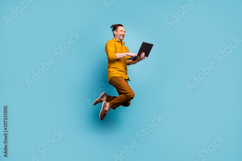 Photo Full body photo of cheerful excited man jump use computer search online social m