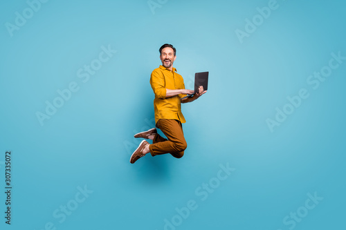 Fototapeta Full size photo of funky man feel rejoice emotions jump use laptop search social media online black friday discounts wear casual style clothing isolated over blue color background obraz