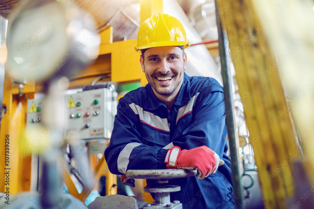 Fototapeta Handsome caucasian smiling unshaven worker in protective uniform leaning on valve while standing in factory.