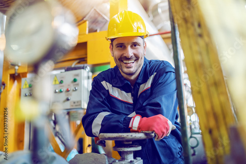 Handsome caucasian smiling unshaven worker in protective uniform leaning on valve while standing in factory.