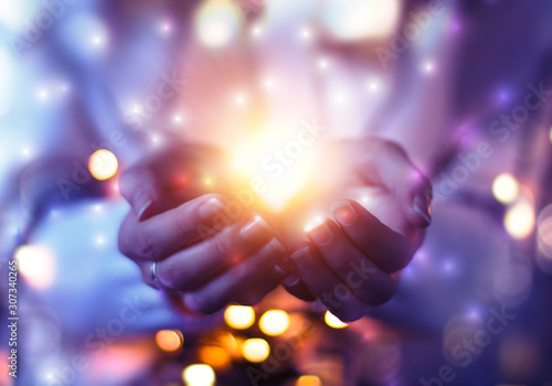 The magical effect emanating from female hands. Magic particles, light stream on an abstract background.