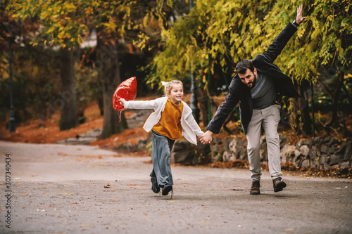Playful father and daughter running in park Wallpaper Mural