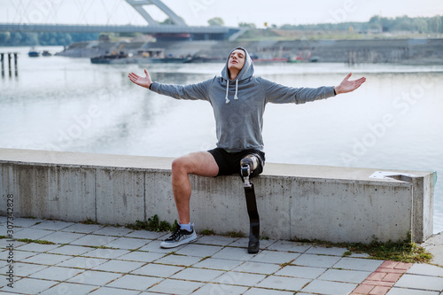 Fit healthy caucasian handicapped sportsman with artificial leg and hoodie on head sitting on quay with arms opened Canvas Print