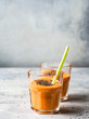 Two glasses of fresh healthy carrot smoothie with chia seeds on grey background. copy sapce