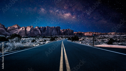 Fotografie, Obraz An endless desolate road leading into Arches National Park in Moab, Utah, USA under a dark and starry night sky