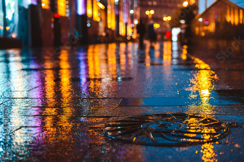 plakat Rainy night in a big city, reflections of lights on the wet road surface.