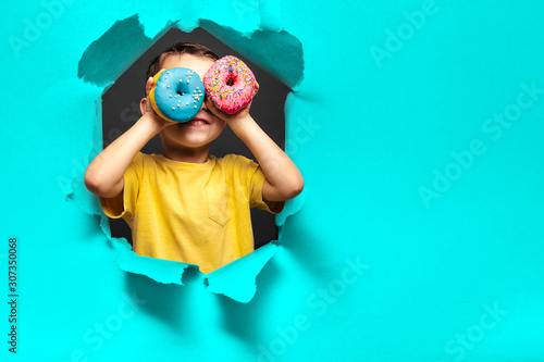 Fototapeta Happy cute boy is having fun played with donuts on black background wall. obraz