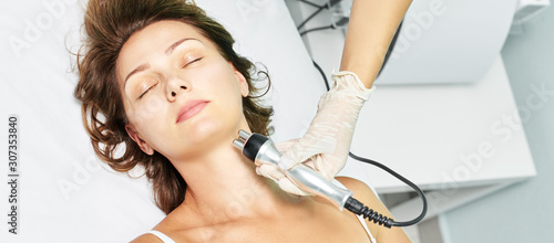 Fototapeta Dermatology skin care facial therapy. Medical spa anto wrinkles procedure. Woman face rejuvenation. Pretty girl. Rf cosmetician equipment. Chin and neck obraz