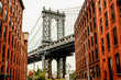 Manhattan bridge seen from Washington St alley enclosed by two brick buildings on a cloudy and rainy day, Brooklyn Dumbo, New York, USA.