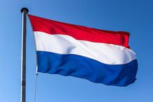 Dutch Flag On A Flagpole Waving In The Wind, Close Up On A Blue Sky Background