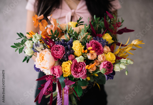 Very nice young woman holding big blossoming bouquet of campanella peach roses, misty bubbles roses, ranunculus, eustoma, pistachio fresh flowers in pink and yellow colors on the grey wall background © anastasianess