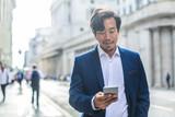 Fototapeta Londyn - Handsome businessman walking in the street, using his phone