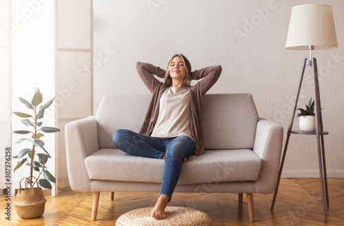 Obraz Millennial girl relaxing at home on couch, enjoying free time - fototapety do salonu