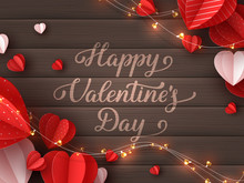 Happy Valentines Day Greeting Card. Decorative Paper Cut Hearts With Garland And Handwritten Lettering Text On Brown Wooden Background. Vector Illustration.