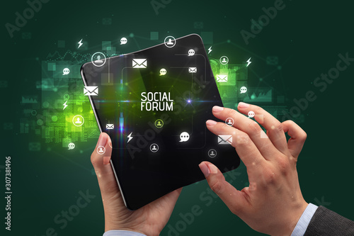 Businessman holding a foldable smartphone with SOCIAL FORUM inscription, social networking concept
