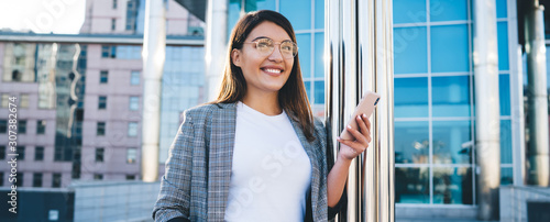 Fényképezés Half length portrait of prosperous business woman in trendy wear standing with mobile phone on modern urban architecture background, smiling hipster girl using smartphone for chatting outdoors