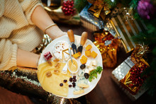 Closeup On Trendy Middle Age Woman Holding Cheese Platter