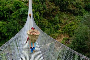 Fototapeta Mosty Nepalese woman carrying a wicker basket on her back, walking on a hanging bridge. Nepal, Himalaya.